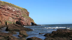 Cave and rock arch in Maw Skelly headland Angus Scotland Stock Footage
