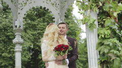 Happy bride and groom are embracing in an open gazebo with silver columns. Stock Footage