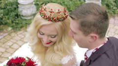 Young bride in the crown and groom in a jacket and tie looking up and smiling. Stock Footage