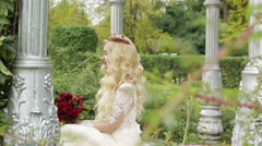 Blonde girl in a wedding dress is visible through the branches of the bushes. Stock Footage
