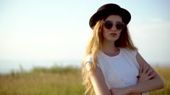 Young beautiful woman model in hat and sunglasses posing outdoor slow motion Stock Footage