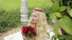 Bride with flowers in hand looking up sitting on the ground. Stock Footage