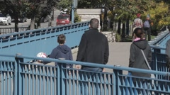 Group of People crossing pedestrian bridge over river. Stock Footage