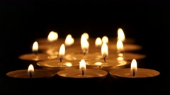 Group of burning candles on black background. Close up Stock Footage