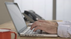 Male wearing wedding ring typing on silver laptop Stock Footage