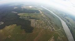 Professional parachute jumper flying above green field, river. Grey sky. Balance Stock Footage