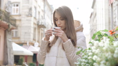 Smart girl drinking a cup of coffee on the street, enjoying and smiling. 4K Stock Footage