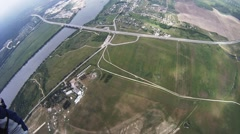 Professional parachute jumper flying above green field, river. Aerial view Stock Footage