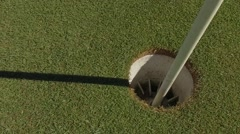 Golf ball rolls into golf course hole slow motion 120fps Stock Footage