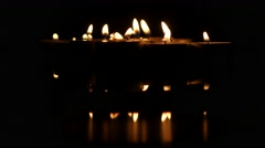 Group of burning small candles on a black background. Close up Stock Footage