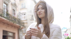 Pretty girl drinking a cup of coffee on the street, enjoying and smiling. 4K Stock Footage