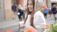 Pretty girl stands with cup of coffee on the street, enjoying and smiling. 4K Stock Footage