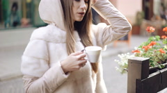 Smart girl drinking a cup of fume coffee and smiling on the street. 4K Stock Footage