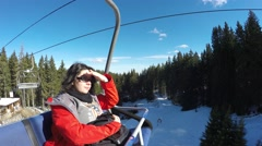 Portrait of beautiful young girl in a red coat, sitting happily on ski lift Stock Footage