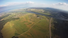Professional parachute jumper flying above green lands. Sunny. Extreme. Height Stock Footage