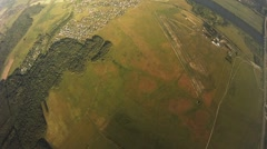 Professional parachute jumper flying above green fields. Wind. Extreme. Sunny Stock Footage