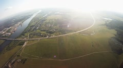 Professional parachute jumper flying above green fields. Hold balance. Height Stock Footage