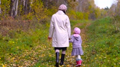 Little girl and woman in gumboots walking Stock Footage