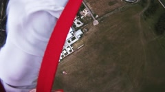 Professional parachute jumper landing on green fields. Evening. Extreme Stock Footage