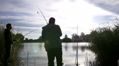 Two fishermen with fishing rods catch fish in the pond in the evening Stock Footage