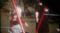 Children play on the swing set in the back yard, 3725 vintage film home movie Stock Footage