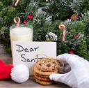Stack of fresh cookies, glass of milk and letter for Santa with hand wearing Stock Photos