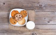 Variety of baked cookies in napkin and glass of milk on rustic wooden boards Stock Photos