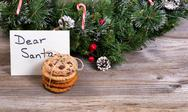 Stack of cookies and letter for Santa with evergreen decoration in background Stock Photos