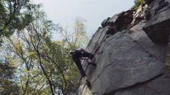 Topless climber abseiling cliff Stock Footage