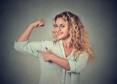 Young happy woman flexing muscles showing her strength Stock Photos