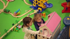 Girls playing dolls house in shopping mall Stock Footage