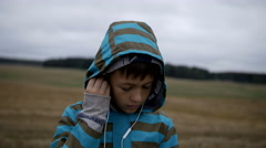 Boy listening to music from your phone, boy in a field on the mountain in the Stock Footage