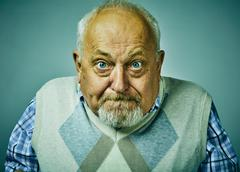 Angry disgruntled senior man face expression. Stock Photos