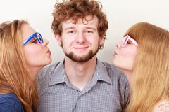 Two pretty young women kissing handsome man. Stock Photos