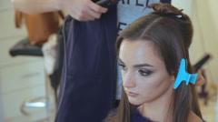 Hairdresser using straightener on woman hair in hair salon Stock Footage