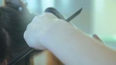 Hairdresser using straightener on girl's hair in hair salon Stock Footage