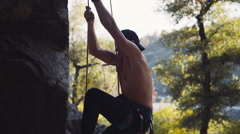 Topless climber descending on cliff Stock Footage