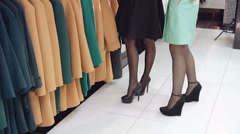 Two fashionable ladies choosing the coats in shop Stock Footage