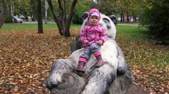 Cute little child seats on the wooden bear in the autumn park. Stock Footage