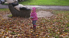 The child throws dry leaves into the air. Walking in the autumn park. Stock Footage