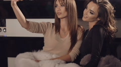 Two models posing in rich fur coats for selfie in rich boutique Stock Footage