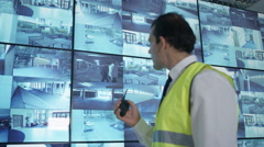 4K Security officer watching CCTV video screens & talking on radio Stock Footage