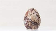 An egg shaped textured stone rotating on white background Stock Footage