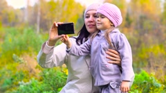 Mother and daughter taking self-portrait on smartphone Stock Footage