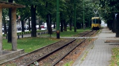 Yellow tram that crosses a verdant park in his way passenger station Stock Footage