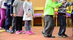 Kindergarten children going in a row listening to the teacher indications Stock Footage