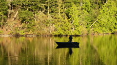 Man fly fishing at dawn, Pass Lake, Deception Pass Stock Footage