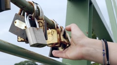 Hand woman studying metal padlock attached to love on the iron railing of a b Stock Footage