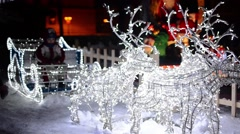Small boy sitting in a sleigh adorned with white lights and pulled by four re Stock Footage