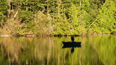Man rowing boat on lake at dawn Stock Footage